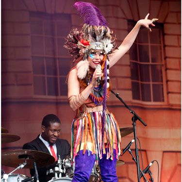 Ever the eclectic dresser, Paloma didn't disappoint in a colourful collaboration of thigh-high purple boots with fringed dress and feathered headdress for her set at Latitude festival