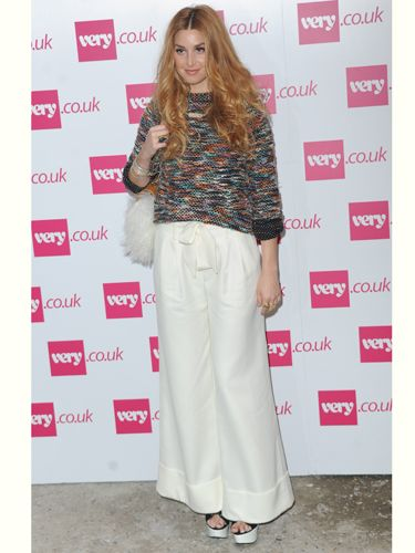 """<p>Whitney Port will be selling her own clothing line, Whitney Eve on <a href=""""http://www.very.co.uk/web/en/celebrity-style.page"""">very.co.uk</a> from October and came to London to show Fearne Cotton support at her show. She worked the 70s trend in these super wide white flares and check out her fluffy bag!</p>"""