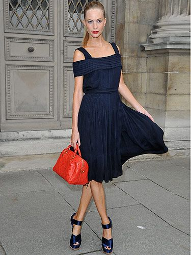 <p>Model Poppy Delevingne arrived at the Louis Vuitton show looking like she just walked off the catwalk herself. She wore a stunning navy velour dress with matching chunky sandals. Poppy tied her hair up in a tight ponytail and held a bright red satchel with matching red lipstick. We literally want her entire outfit from top to bottom. Love!</p>