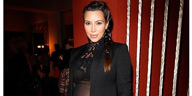 <p>Who says you can't look and feel sexy as a pregnant lady? Kim Kardashian does both as she dons a slimming all-black look featuring black trousers and a blazer that are given an evening edge with a sheer top with lace appliqué. You go girl!</p>