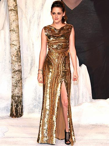 <p>Actress Kristen Stewart appeared at the premiere of The Twilight Saga: Breaking Dawn – Part 2 in Berlin flaunting a gorgeous gold sequin Elie Saab dress with a massive side slit. Paired with black Christian Louboutin shoes and a high bouffant ponytail, she definitely showed up Angelina Jolie with her fierce pose, don't you think?</p>