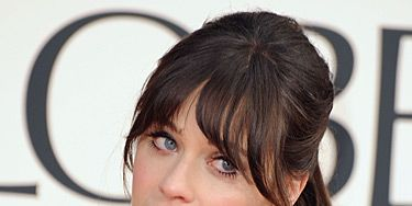 """<p>We love Zooey Deschanel's fun and flirty red carpet beauty look. She showed up at the 2013 Golden Globe Awards with her hair tied up into a loose ponytail and curled the ends. She left out her full fringe and finished off the look with matte red lips.</p> <p>Oh, and did you catch her black-and-white glitter <a href=""""http://www.cosmopolitan.co.uk/beauty-hair/news/beauty-news/zooey-deschanel-wears-film-strip-nail-art-at-2013-golden-globe-awards"""" target=""""_blank"""">camera and film strip nail art</a>? FAB!</p>"""