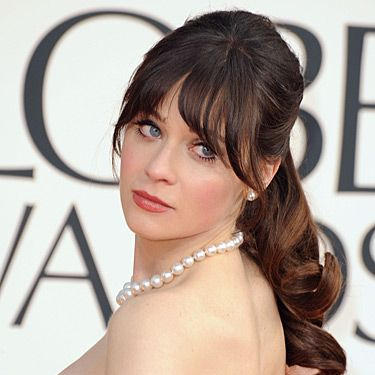 """<p>We love Zooey Deschanel's fun and flirty red carpet beauty look. She showed up at the 2013 Golden Globe Awards with her hair tied up into a loose ponytail and curled the ends. She left out her full fringe and finished off the look with matte red lips.</p><p>Oh, and did you catch her black-and-white glitter <a href=""""http://www.cosmopolitan.co.uk/beauty-hair/news/beauty-news/zooey-deschanel-wears-film-strip-nail-art-at-2013-golden-globe-awards"""" target=""""_blank"""">camera and film strip nail art</a>? FAB!</p>"""
