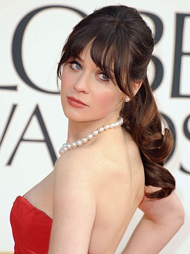 "<p>We love Zooey Deschanel's fun and flirty red carpet beauty look. She showed up at the 2013 Golden Globe Awards with her hair tied up into a loose ponytail and curled the ends. She left out her full fringe and finished off the look with matte red lips.</p> <p>Oh, and did you catch her black-and-white glitter <a href=""http://www.cosmopolitan.co.uk/beauty-hair/news/beauty-news/zooey-deschanel-wears-film-strip-nail-art-at-2013-golden-globe-awards"" target=""_blank"">camera and film strip nail art</a>? FAB!</p>"