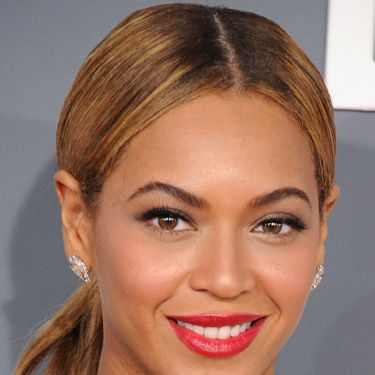 <p>Also in the red lipstick camp, Beyoncé showed off classic makeup, with perfectly groomed arches and a super-slick centre-parted pony. Simple but chic.</p>