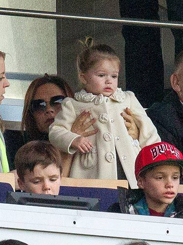 <p>What does Harper Beckham wear to a football match? Certainly not a garish footy shirt, that's for sure. Harper watched daddy's Paris Saint-Germain game wearing this cream coat – it must be new because we haven't seen it before. The rose details on the collar and buttons are tres cute. Harper stays true to what we know her for, by wearing a grey dress underneath.</p>