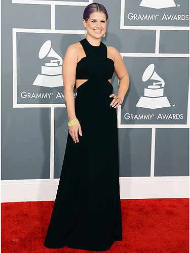 <p>Kelly Osbourne showed off her trim figure in a simple yet effective cut-out black Paule Ka dress at the 2013 Grammy awards. The Fashion Police presenter accessorised with a chunky H Stern gold bracelet and matching earring and we just love her sleek purple ponytail.</p>