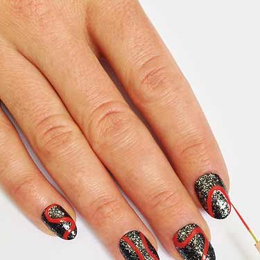 """<p>Take a striping brush dipped in red nail polish and paint on a """"S"""" shaped squiggly line from cuticle to tip. Paint on different shaped curved red outlines on the rest of the nails, some from tip to cuticle others from side to side.</p>"""