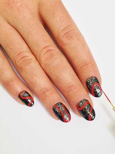 "<p>Take a striping brush dipped in red nail polish and paint on a ""S"" shaped squiggly line from cuticle to tip. Paint on different shaped curved red outlines on the rest of the nails, some from tip to cuticle others from side to side.</p>"