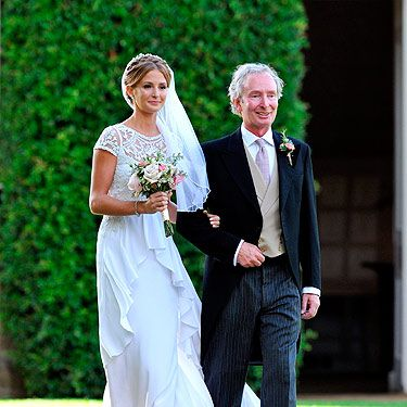 <p>We got our frist glimpse at Millie Mackintosh's vintage Alice Temperley wedding dress as she was pictured walking towards the church with her father Nigel.</p>