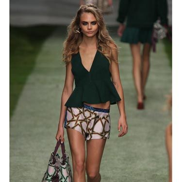 <p>Cara Delevingne's first look - silk printed boxer shorts and a forest green peplum top. </p><p> </p>