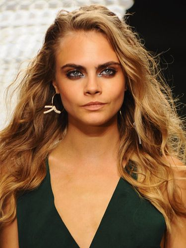 "<p>Cara Delevingne channelled Ibizan beachy beauty for the Topshop Unique show with ease. Makeup artist Hannah Murray used the matte Topshop Bronzer on Cara over her St Tropez Instant Tan. The incredible eye makeup was courtesy of the smudgy Topshop Grunge Stick etched along the upper and lower lids, plus a burnished brown shadow with a little touch of gloss, creating a contrasting texture against the powdery pigments. The tousled locks were created by rough drying L'Oreal Professionnel Force 5 Mousse into the strands for texture before being randomly tonged. Then a conditioner was scrunched into the waves to give a wet effect.</p> <p><a href=""http://www.cosmopolitan.co.uk/beauty-hair/news/see-the-ibizan-beauty-look-at-topshop-unique-ss14#ixzz2fnfTDtFt"" target=""_blank"">BEHIND THE SCENES AT TOPSHOP UNIQUE</a></p>"