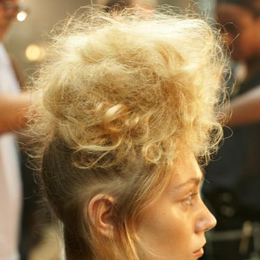 <p><strong>The hair look:</strong> Styled by global ghd creative director Sam McKnight and his team, hair was reminiscent of Greek statues with major backcombing for tall statuesque silhouettes.</p><p><strong>Get the look:</strong> 1) Using the ghd tail comb, take out the hairline from temple to temple, leaving a soft airy section around the hairline. 2) Gather all the remaining hair into a high pony at the top of the head, using the ghd oval dressing brush to smooth for a sleek finish. Secure with an elastic band. 3) Take small sections of hair from the pony at a time and wrap around one finger. Once wrapped, gently release your finger holding the curl in place. Using the ghd eclipse styler, close onto the curl and hold for approximately five seconds, then pin up and leave to cool. 4) Once repeated throughout the whole ponytail, release the pins and brush through the hair to free all movement and soften the curls. Backcomb at the roots using the ghd tail comb to create extra volume and give a light fluffy texture to the hair. 5) Taking small sections, pin and tease the hair forward and upwards, creating a tiara shaped head-dress with the hair piled high. 6) Spray the whole style with hairspray to the point that hair is almost wet and wrap with a hairnet. Ensure the sides are kept tight to the head and the front elevated to create the tiara shape. Next, use the ghd air hairdryer to set the shape in place, making use of the cool shot button and run the ghd eclipse styler over the remaining hair underneath creating a smooth, wispy finish.</p>
