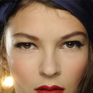 """<p><strong>The makeup look:</strong> """"A 1950s pin-up beauty…think Dita Von Teese, but in a naughty way, a pin-up that danced to much and is back from the party"""" said Makeup Artist Carole Colombani using MAC.</p><p><strong>The products:</strong> Face - Pinch Me Powder Blush blended over the centre of cheeks for a healthy flush. Eyes - Veluxe Brow Liner used to define the brows in a """"retro"""" way: Perfected two-thirds of the way starting at the inner brow, then sketched in a broken line after the arch before being brushed upwards, lifting the brow. Blacktrack Fluidline drawn through the upper lashline starting at the extreme inner corner and extending outwards to lift and elongate eyes. False Lash Black Mascara blended through the upper lashes only to lengthen and define. 20 Lash half-demis applied above the outer corners of lashes to extend and lift eyes with a beautiful flick. Lips - MAC PRO Crimson and Red Lipmix mixed together for intensity. MAC PRO Basic Red Chromagraphic Pencil used to define, creating a slightly bigger and fuller lower lip to finish.</p>"""