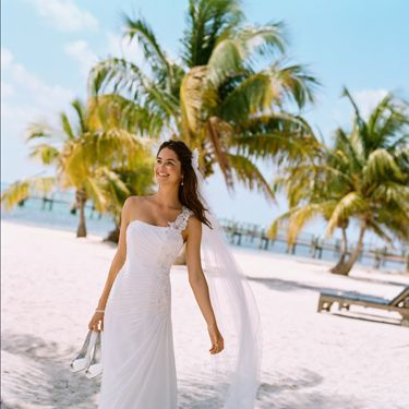 """<p>Think about the setting and location of your wedding and try to choose a dress that fits in with the overall theme. if you're planning on a beach wedding, then a softer look or less structured style might go down better in Hawaii, rather than a traditional gown which would suit a church much better.</p><p><em>V3398, David's Bridal Collection, Soft White, £475.00, <a href=""""http://www.davidsbridal.co.uk"""" target=""""_blank"""">davidsbridal.co.uk</a></em><strong> </strong><strong></strong></p>"""