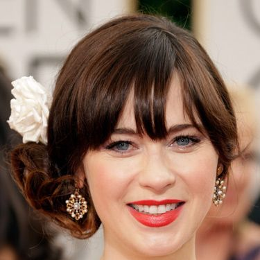 """<p>You can always rely on Zooey for a fun beauty look. The actress accessorised her side chignon with a spring-fresh flower and for her face she let her lips and lashes do the talking.</p><p><a href=""""http://www.cosmopolitan.co.uk/fashion/news/golden-globes-red-carpet-dresses"""" target=""""_blank"""">GOLDEN GLOBES 2014 RED CARPET PICTURES</a></p><p><a href=""""http://www.cosmopolitan.co.uk/beauty-hair/news/trends/celebrity-beauty/best-golden-globes-hair-makeup-beauty"""" target=""""_self"""">THE EVER BEST GOLDEN GLOBES BEAUTY LOOKS</a></p><p><a href=""""http://www.cosmopolitan.co.uk/beauty-hair/news/trends/celebrity-beauty/celebrity-nail-art-manicures"""" target=""""_blank"""">THE BEST GOLDEN GLOBES NAIL ART PICTURES</a></p>"""