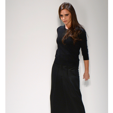 """<p>Victoria Beckham brought her Autumn/Winter 2014 collection to New York Fashion Week (with David and their too-cute kids watching from the frow), and showed how far she's come as a <em>bona fide</em> fashion designer.</p><p>Showing looser silhouettes - but still with her trademark structure - the collection included pleated dresses and skirts, oversized coats, sleeveless jackets, slouchy trousers and - get this! - flat shoes. We know right? We told you VB's signature style has relaxed somewhat.</p><p>With a colour palette consisting of mainly monochrome there were still plenty of surprises like punchy pops of red and gold chain details.</p><p>""""I like the element of surprise that you get with something that seems strict from the front but has a cut-away or soft, blouson back,"""" said VB backstage.</p><p>Her AW14 collection went down a storm with the assembled fash pack - though we were a tad disappointed when Victoria disn't come out and point, Spice Girl-style. Oh well, there's always next season...</p><p><strong>CLICK THROUGH TO SEE CATWALK PICTURES >>></strong></p><p> </p>"""