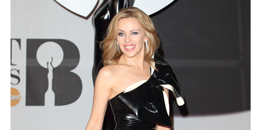 """<p>SOUND THE KYLIE KLAXON! Ms Minogue vamps things up in a black PVC dress, complete with HUGE bow and successfully manages to NOT look like she's wearing a bin-liner (which she'd no doubt rock, anyway).</p> <p><a href=""""http://www.cosmopolitan.co.uk/fashion/news/baftas-red-carpet-2014?click=main_sr"""" target=""""_blank"""">SEE CELEBS LOOKING FINE AT THE BAFTAS 2014</a></p> <p><a href=""""http://www.cosmopolitan.co.uk/fashion/news/celebs-new-york-fashion-week-aw14"""" target=""""_blank"""">CELEBRITY FRONT ROW FASHION AT LFW</a></p> <p><a href=""""http://www.cosmopolitan.co.uk/fashion/news/cosmopolitan.co.uk/fashion/news/golden-globes-red-carpet-dresses?click=main_sr"""" target=""""_blank"""">RED CARPET AT THE GOLDEN GLOBES 2014</a></p>"""