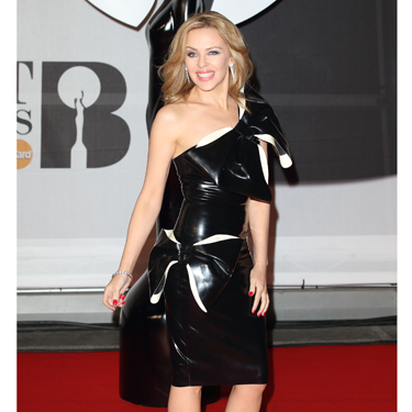 """<p>SOUND THE KYLIE KLAXON! Ms Minogue vamps things up in a black PVC dress, complete with HUGE bow and successfully manages to NOT look like she's wearing a bin-liner (which she'd no doubt rock, anyway).</p><p><a href=""""http://www.cosmopolitan.co.uk/fashion/news/baftas-red-carpet-2014?click=main_sr"""" target=""""_blank"""">SEE CELEBS LOOKING FINE AT THE BAFTAS 2014</a></p><p><a href=""""http://www.cosmopolitan.co.uk/fashion/news/celebs-new-york-fashion-week-aw14"""" target=""""_blank"""">CELEBRITY FRONT ROW FASHION AT LFW</a></p><p><a href=""""http://www.cosmopolitan.co.uk/fashion/news/cosmopolitan.co.uk/fashion/news/golden-globes-red-carpet-dresses?click=main_sr"""" target=""""_blank"""">RED CARPET AT THE GOLDEN GLOBES 2014</a></p>"""