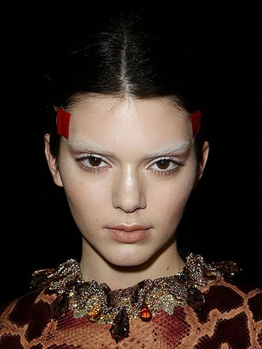 <p><strong>The look:</strong> Models including Kendall Jenner (pictured) had their brows bleached by the legendary Pat McGrath who then contoured the skin in varying neutral shades. To get a feline shape with their eyes, hairstylist Luigi Murenu tightly taped string from the temples around the back of the head and created knotted plaits below.</p>