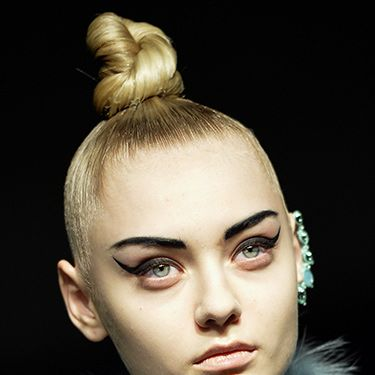 <p><strong>The look:</strong> Tightly coiled topknots paired with severe eyebrows and ultra-winged black eyeliner flicks. There's nothing soft about this look other than the nude lip.</p>