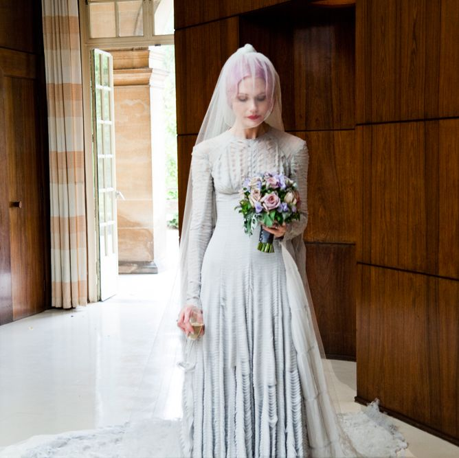 <p>A stunning pale grey slashed chiffon wedding-dress, designed by Gareth Pugh is worn with a striking veil by milliner, Stephen Jones, 2011.</p>