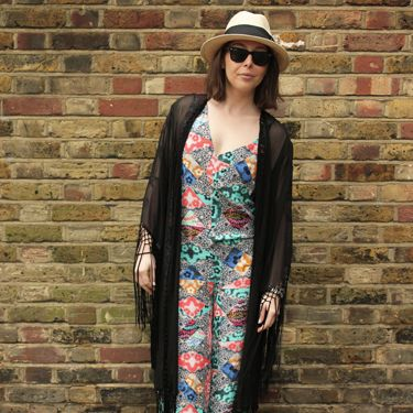 <p>Jumpsuit, Asos. Fringed shawl, Unif at Urban Outfitters. Straw hat, H&M. Slides, Kurt Geiger.</p>