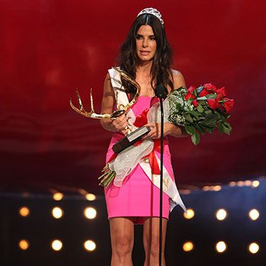 """<p>Sandra Bullock was adorned with all kinds of <em>Miss Congeniality </em>paraphernalia to collect her 'Decade of Hotness' award at the ceremony, and hot she looks indeed in her bold pink strapless dress.</p><p><a href=""""http://www.cosmopolitan.co.uk/fashion/news/best-of-the-cfda-red-carpet?page=1"""" target=""""_blank"""">15 BEST DRESSED AT THE CFDA AWARDS</a></p><p><a href=""""http://www.cosmopolitan.co.uk/celebs/entertainment/rihanna-hits-back-at-critics-over-that-nipple-baring-dress?click=main_sr"""" target=""""_blank"""">RIHANNA'S CONTROVERSIAL SEE-THROUGH DRESS</a></p><p><a href=""""http://www.cosmopolitan.co.uk/fashion/shopping/festival-season-essentials"""" target=""""_blank"""">FESTIVAL SEASON FASHION ESSENTIALS</a></p>"""