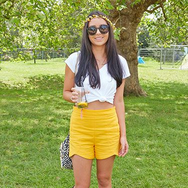 <p>Hello sunshine! We LOVE Cara Bramwell, 25, from New Zealand's summery yellow shorts from Zara. Cute! Paired with Hunters and a floral headband. (Extra points for matching shorts with drink, well-played.)</p>
