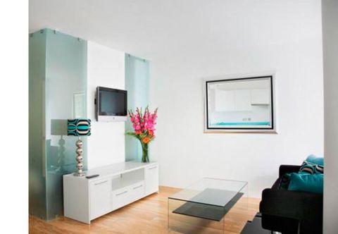 Room, Interior design, Floor, Wall, Display device, Furniture, Flooring, Living room, Teal, Interior design,