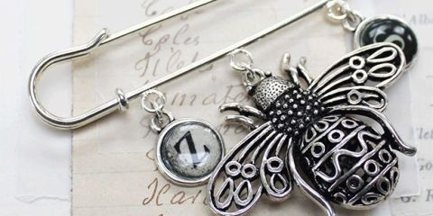 Metal, Brooch, Silver, Wing, Rectangle, Arthropod, Steel, Body jewelry, Chemical substance, Natural material,