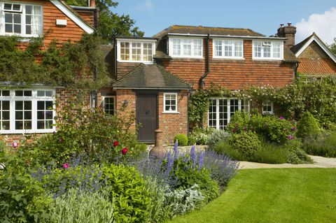 Entrance to house with flowering borders and chiminea, The Lowes Garden, The Coach House, Haslemere, Surrey, UK