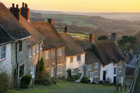 Countryside village street with closely connected houses, overlooking fields and sunrise