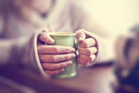Green mug of hot drink being held in pair of hands of jumpered person