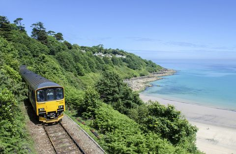 Train moving along the tracks overlooking Cornish beach