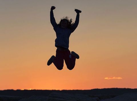 Silhouette of jumping girl against sunset