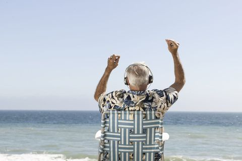 Happy old man listening to music overlooking the sea