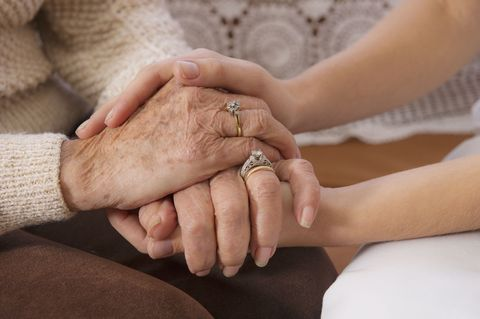 Close up of old woman holding hands with carer