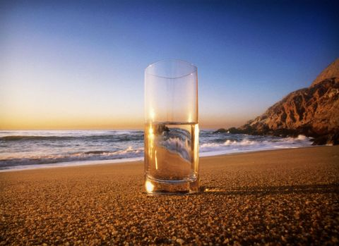 Glass of drinking water on the beach