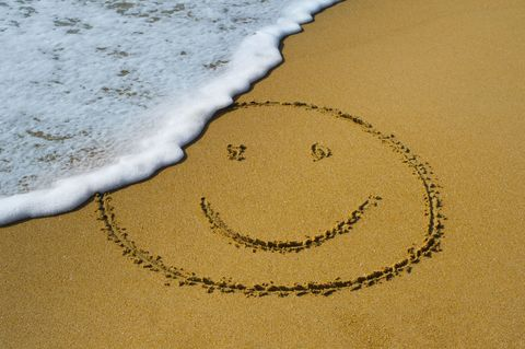 Smiley face in sand on beach