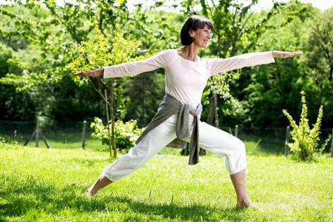 Woman doing tai chi in garden