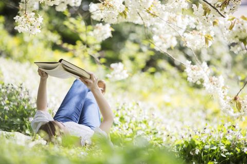Woman reading book under blossom tree