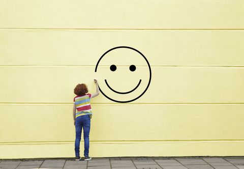 girl drawing smiley face on yellow wall