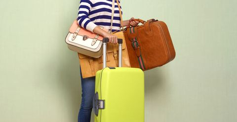 Multiple luggage items in woman's hands