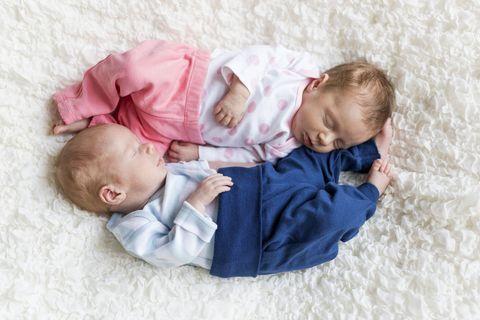 Baby boy and girl asleep on rug