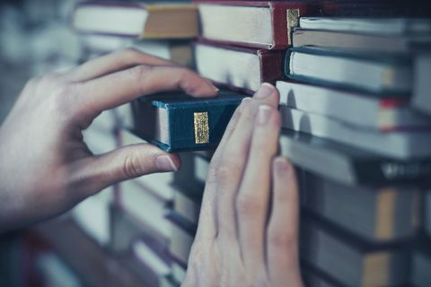 woman picking book from shelf