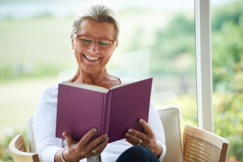 Woman reading book and laughing
