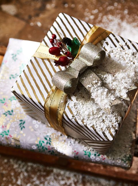 """<p>Wrap up gifts with shimmering papers in simple designs such as stripes and stars; dress them up with metallic, wired ribbons and pre-made bows and bunches of faux berries or hips to make them extra special.</p><p>For an added festive touch, you could clip on decorations that are usually reserved for the tree, such as bells, baubles and birds.<span class=""""redactor-invisible-space"""" data-verified=""""redactor"""" data-redactor-tag=""""span"""" data-redactor-class=""""redactor-invisible-space""""></span></p><p><strong data-redactor-tag=""""strong"""" data-verified=""""redactor"""">MORE:</strong><a href=""""http://www.countryliving.co.uk/create/craft/how-to/a956/country-inspired-christmas-gift-wrapping-ideas/"""" target=""""_blank"""" data-tracking-id=""""recirc-text-link""""><strong data-redactor-tag=""""strong"""" data-verified=""""redactor"""">15 country-inspired Christmas gift wrapping ideas</strong></a></p>"""