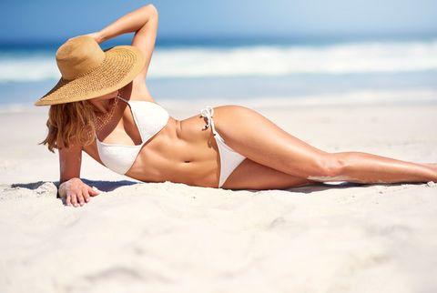 Brassiere, Skin, Human leg, Sand, Elbow, Hat, Bikini, Swimwear, Swimsuit top, People on beach,