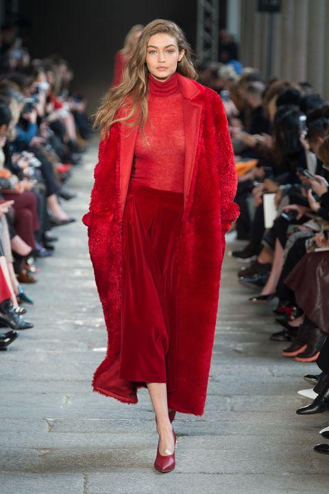 Fashion model, Runway, Fashion, Fashion show, Clothing, Red, Street fashion, Outerwear, Haute couture, Shoulder,
